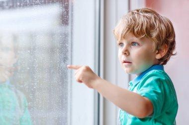 Little blond kid boy sitting near window and looking on raindrop