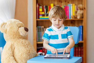 Adorable child playing with tablet computer in his room at home