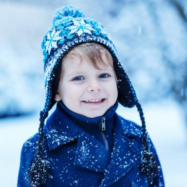 Portrait of little toddler boy in winter clothes with falling sn