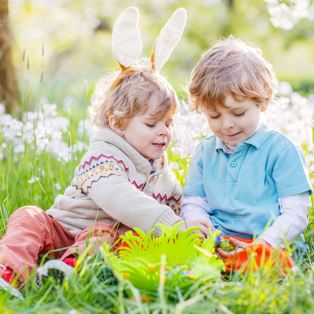 two funny children friends in easter bunny ears during egg hunt
