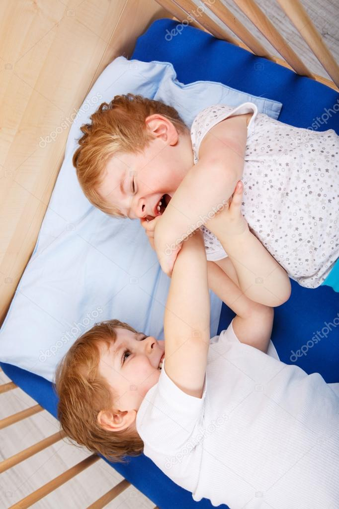 Family Of Two Little Boys Twins Having Fun Playing And Fighting In Bed At Home Indoors Photo By Romrodinka