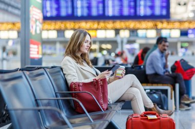 woman at international airport, reading ebook and drinking coffe