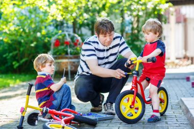 Father teaching his little sons to repair bikes