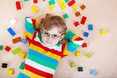Malý blonďatý kluk hrát se spoustou barevných plastových bloku
