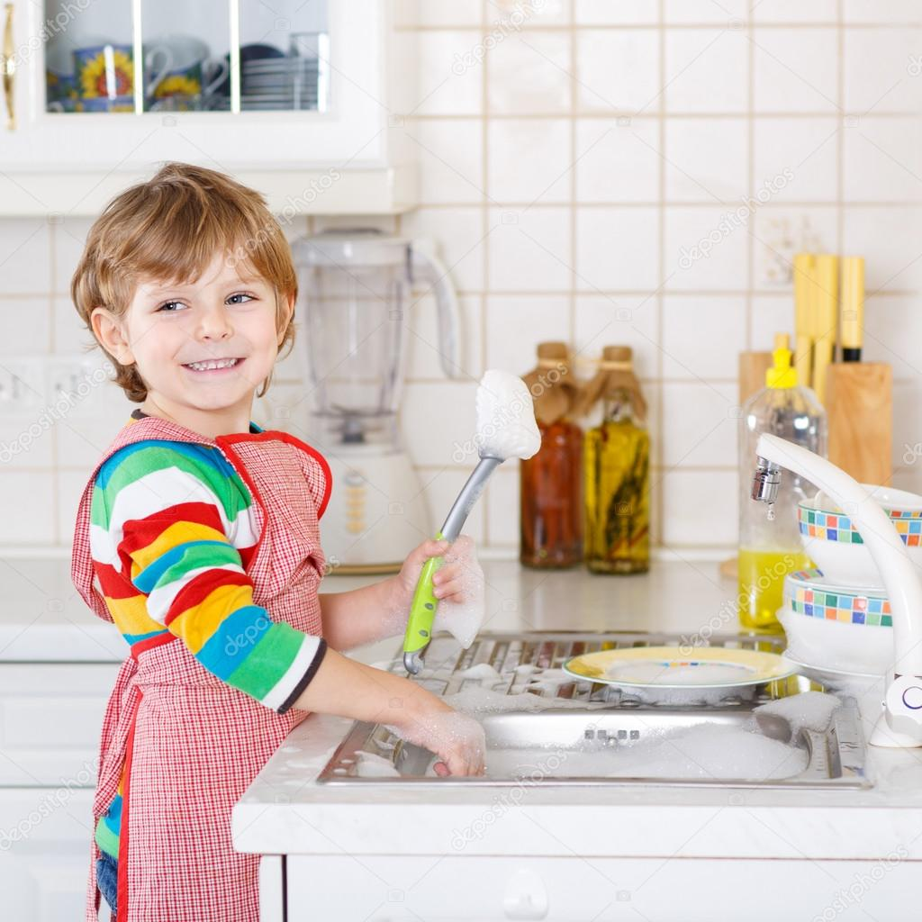 Happy little blond kid boy washing dishes in domestic kitchen ...