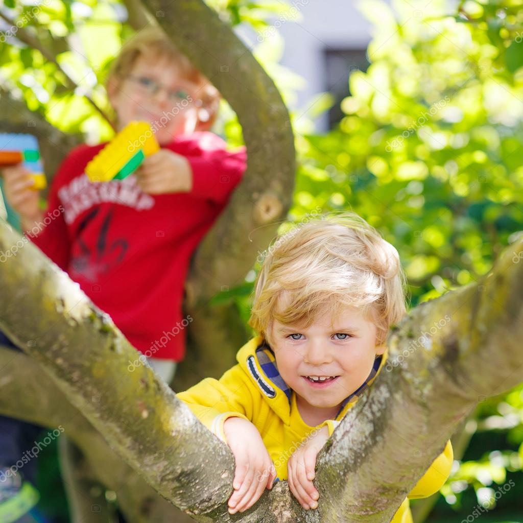 Two Active Little Friends Kid Boys Enjoying Climbing On Tree Toddler Children Learning To Climb Having Fun In Domestic Garden Warm Sunny Day