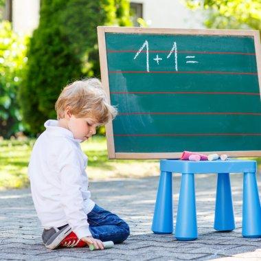 Two siblinig boys at blackboard practicing mathematics