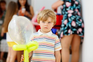 joyful or sad kid boy on birthday party with an air balloon
