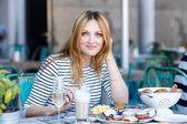 Fotografie Junge Frau, die dem gesunden Frühstück im Café im freien