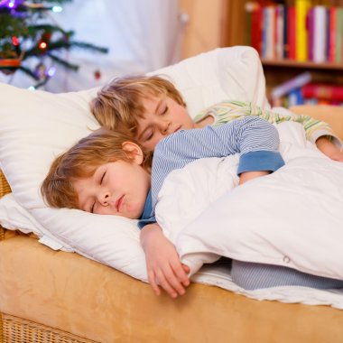 Two little blond sibling boys sleeping in bed on Christmas