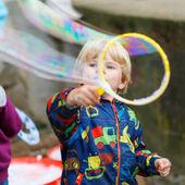 dítě chlapec fouká mýdlové bubliny venkovní