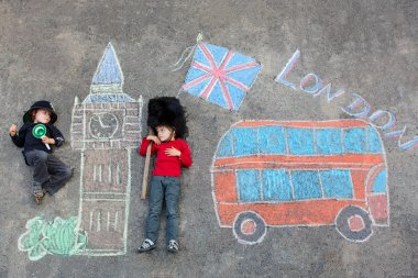 Two little kids with London picture drawing with chalks