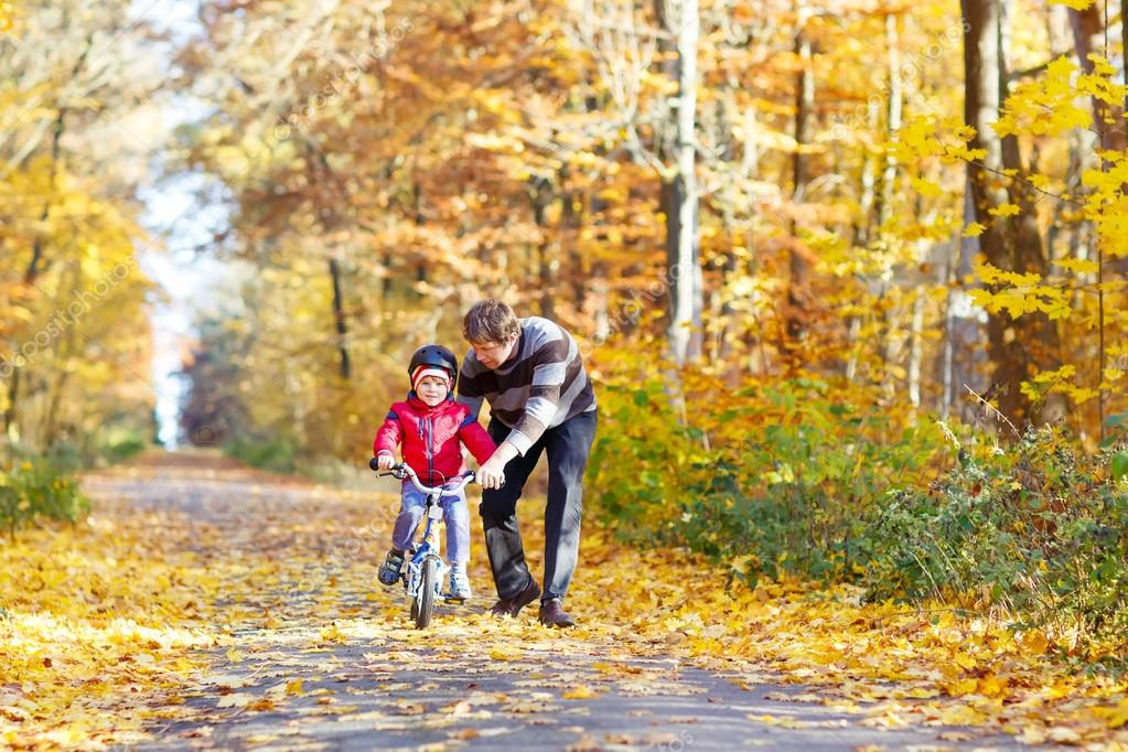 Little kid boy and father with bicycle in autumn forest