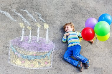 Kid boy having fun with colorful birthday cake drawing with chal