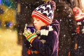Fotografie Kleiner Junge mit heißer Schokolade auf dem Weihnachtsmarkt