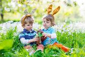 Fotografie Zwei kleine Kinder spielen mit Ostern Schokoladenhasen im freien
