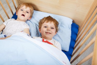 little boys having fun in bed at home