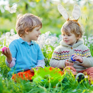 Two little kid boys on Easter during egg hunt