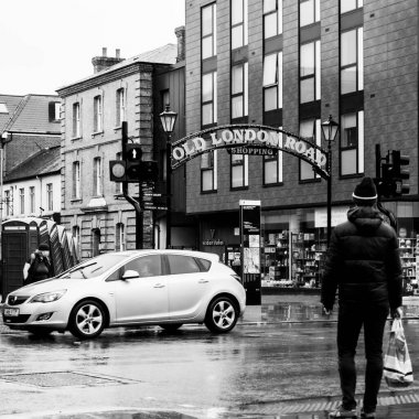 Balck And White Image People Waiting To Cross A Busy Road With Traffic At Pedestrian Traffic Lights