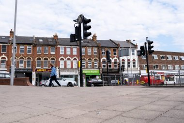 Kingston-Upon Thames London, April 27 2021, Row Of Shops Or Stores On An Empty Town Centre High Street With Passing Cars