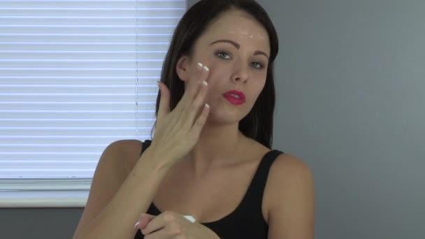 Atraktivní mladá žena použitím krém na obličej