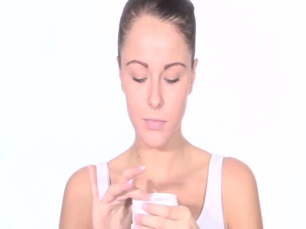 Mladá žena použití kůže hydratační krém