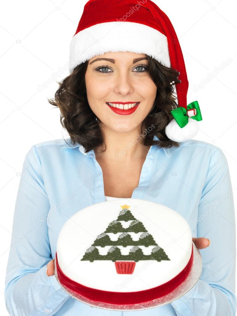 Junge Frau in Nikolausmütze hält einen Weihnachts-Obst-Kuchen ...