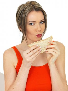 Young Woman Eating a Salmon and Cucumber Brown Bread Sandwich