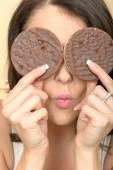Fiatal nő eszik csokoládé fedett rizs sütemény