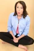 Fiatal őrült nő ül a földön, kék inget visel, és