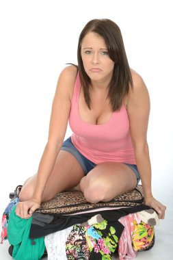 Frustrated Young Woman Trying to Close and Over Filled Suitcase