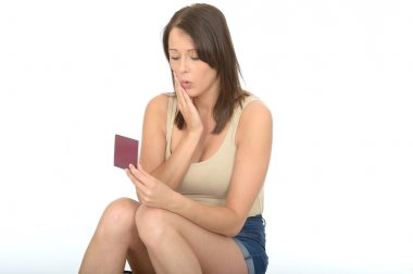Portrait of an Attractive Young Woman Looking Concerned and Worried Looking at Her Passport Travel Documents