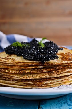 A stack of pancakes with black caviar
