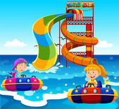 Boy and girl riding on water slide in the ocean