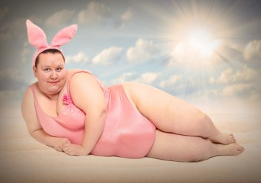 Woman Easter Bunny relaxing on the beach