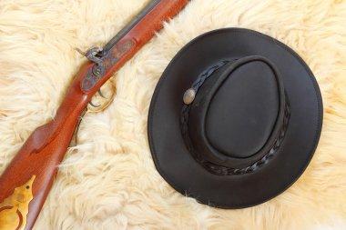 Cowboy hat and hunting gun