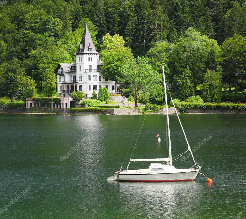 The Grundlsee lake with beautiful castle and sailboat.