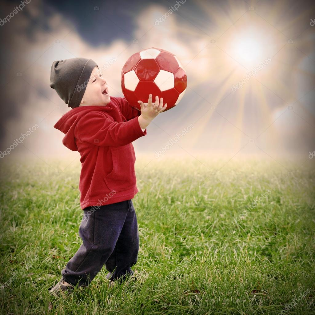 Little boy with soccer ball playing outdoor