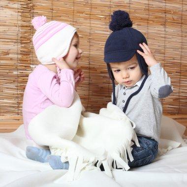 Little kids dressed in warm knitwear