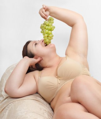 Overweight woman eating grape.