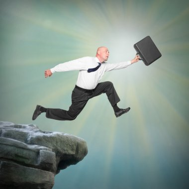 Senior businessman jumping from a edge of cliff