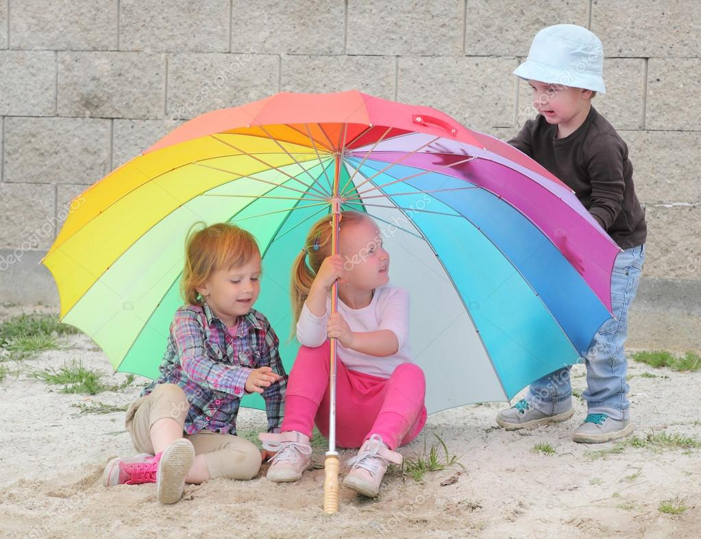 Little kids with umbrella on the beach.