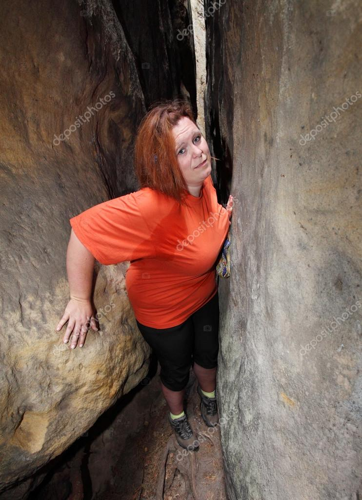 Overweight woman climbing in a narrow canyon