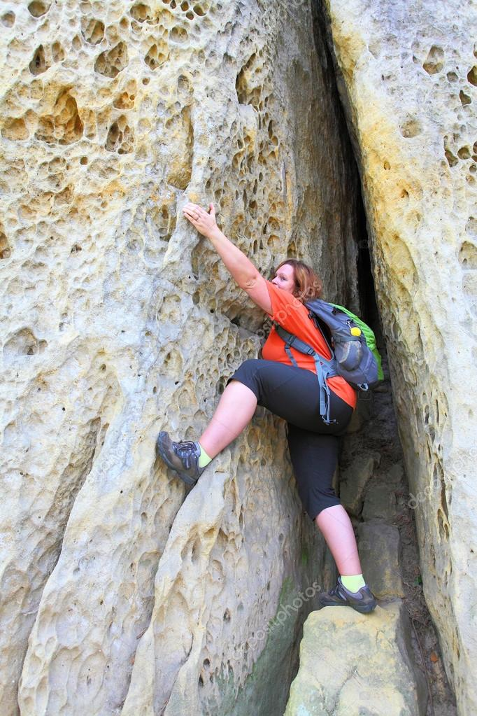 Overweight woman climbing on the rock