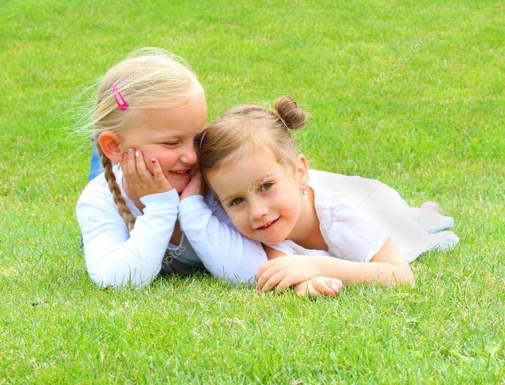 Two little girls lying on grass