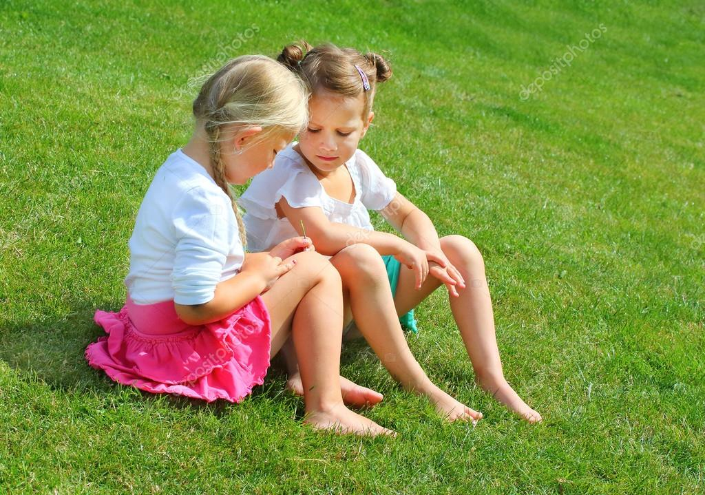 Two little girls sitting and talking on grass