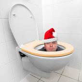 Santa Claus looking from the toilet bowl