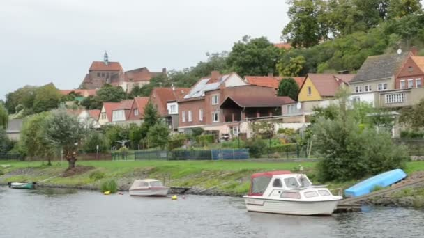 historical cityscape of Havelberg with traditional brick houses and harbor. the boat turning around in circle. bridge with traffic.