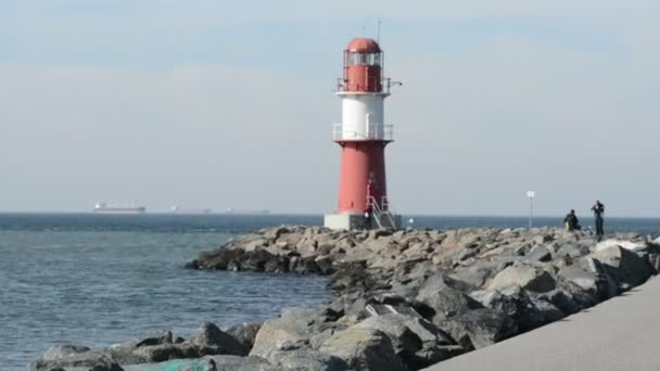 Lidé chodí k majáku Warnemuende. kolečko a motorový člun jezdí z Baltského moře do přístavu. Nachází se na Warnemuende