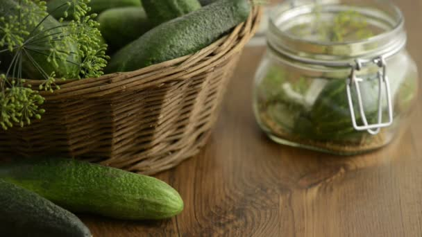 Spices like dill, chili, mustard seeds falling into a canning jar on a table. Aside standing a basket with cucumbers and all around laying also bay leaves and dill, chili peppers